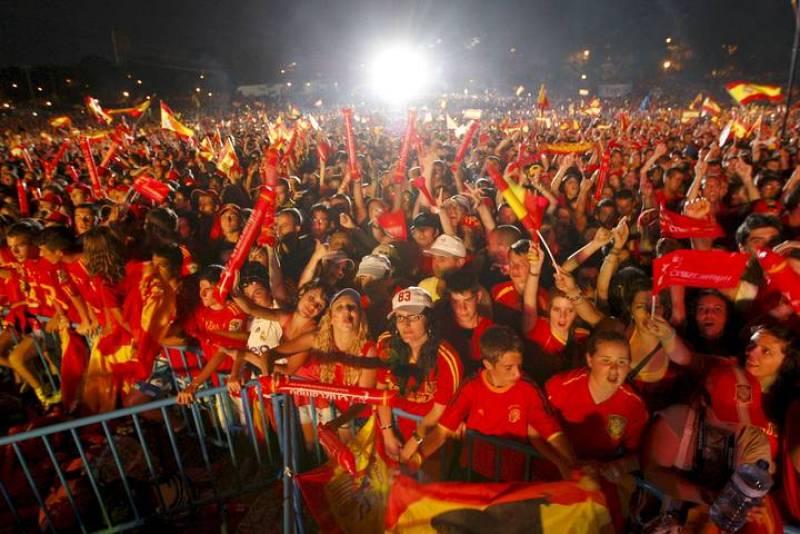 Miles de aficionados saludan a los jugadores de la selección española de fútbol a su llegada al escenario.