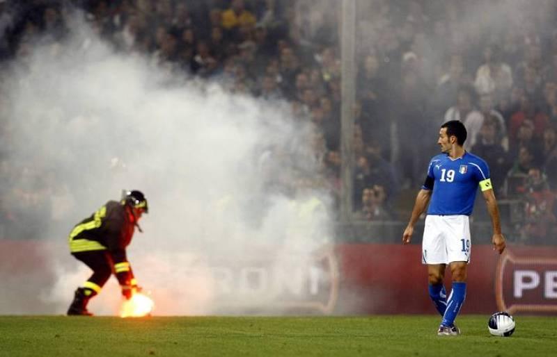 Zambrotta observa como retiran una bengala que los ultras lanzaron al campo.