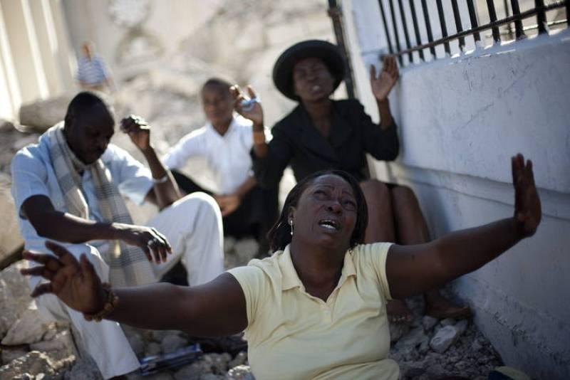 Varias personas asisten a una ceremonia junto a los escombros de la catedral de Puerto Príncipe.