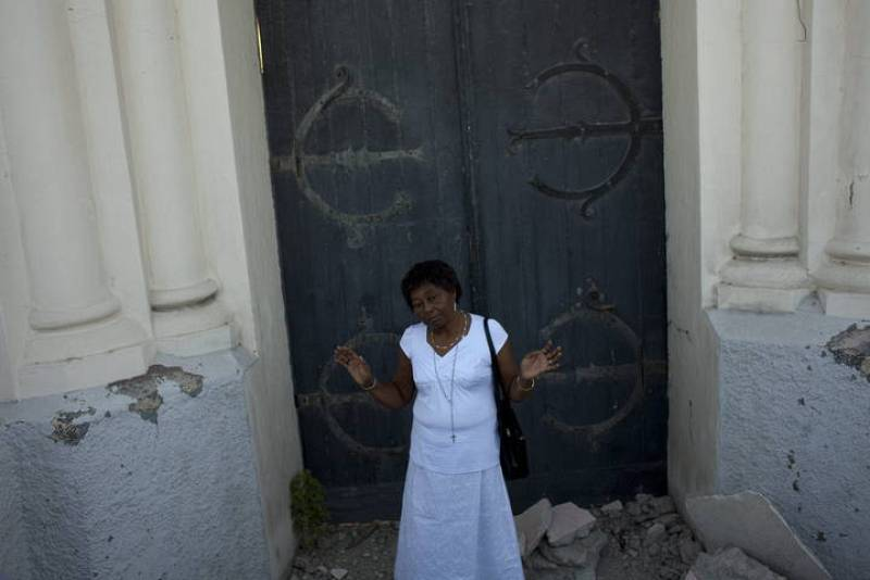 Una mujer reza en frente de la puerta de la catedral de Puerto Príncipe.