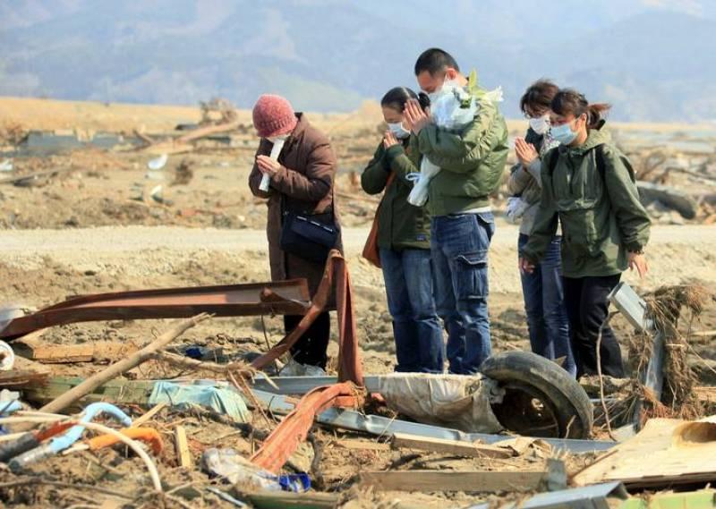 Familiares de una víctima del tsunami rezan en el lugar donde un alumno de la escuela primaria Otawa fue encontrado muerto, a unos 50 metros de la escuela, hoy, miércoles 13 de abril de 2011 en Ishinomaki, prefectura de Miyagi (Japón)