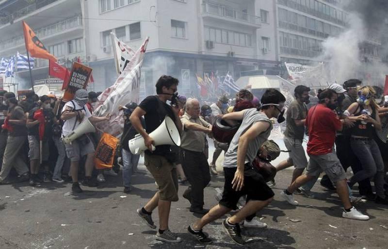 Los manifestanes llevan pancartas y un megáfono para protestar contra el nuevo plan de ajuste aprobado por el Parlamento