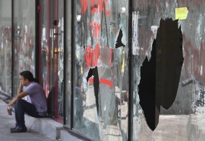 Un hombre habla por teléfono junto a un escaparate destrozado tras dos días de violentos enfrentamientos en la plaza Syntagma en Atenas.