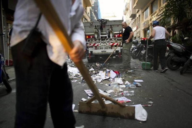 Varios operarios limpian las calles tras los fuertes enfrentamientos protagonizados ayer por la policía y los manifestantes delante del Parlamento griego en Atenas (Grecia).