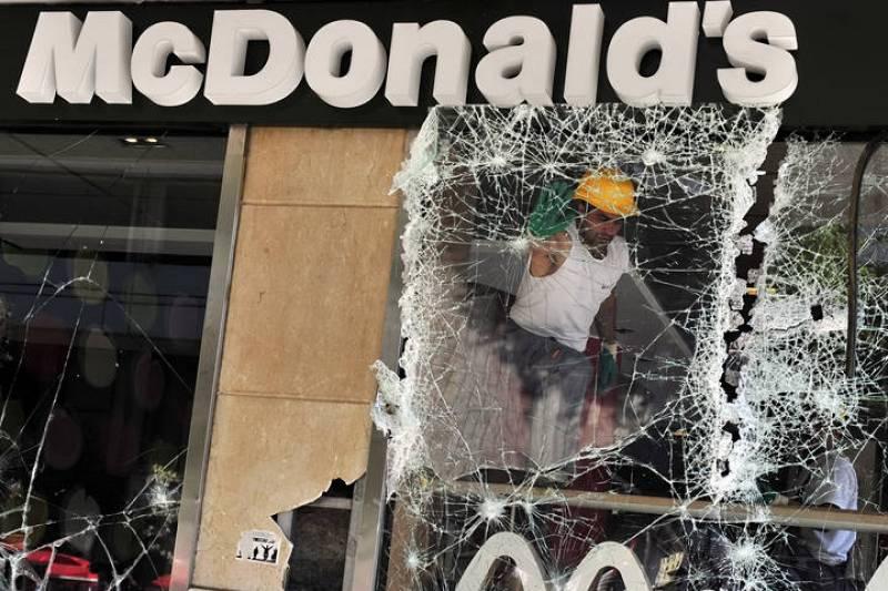 Un hombre retira una ventana rota de Mcdonald's, un establecimiento de comida rápida ubicado en la plaza Syntagma en el centro de Atenas.