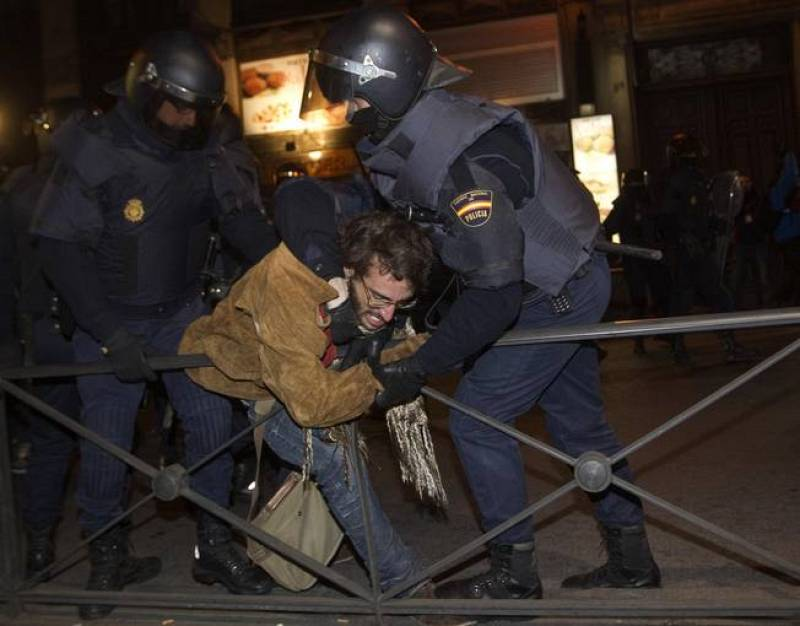 Spanish National Police officers in riot gear struggle with a protester during a demonstration against labour reform in Madrid