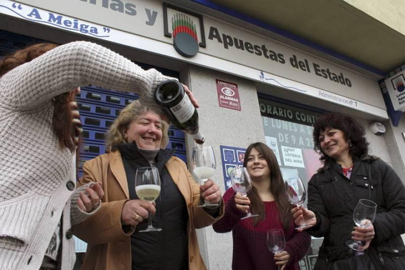 Varias personas beben cava en las inmediaciones de una administración de loterías de Ponferrada que ha repartido dos millones de euros.