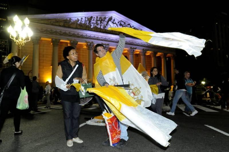 Un hombre vende banderas del Vaticano a las afueras de la catedral de Buenos Aires