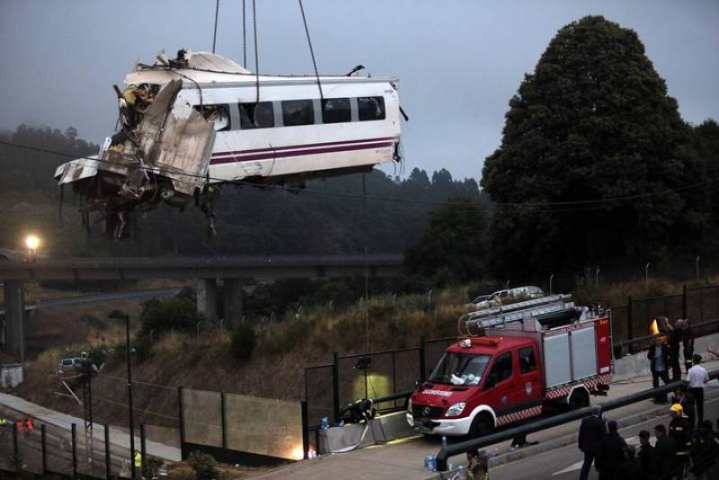 A crane removes a carriage from the tracks at the site of a train crash near Santiago de Compostela