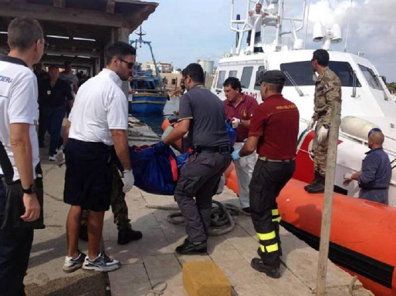 Miembros de los servicios de emergencia recuperan el cadáver de un inmigrante