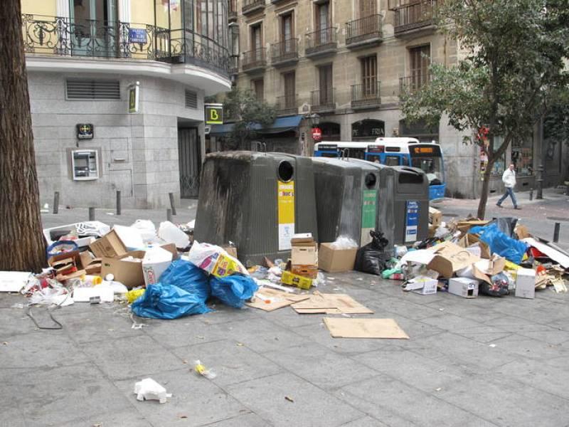 Basura acumulada en la Plaza Carlos Cambronero, donde uno de los contenedores está quemado