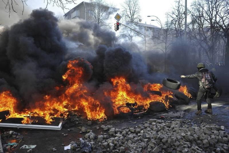 Un manifestante lanza un neumático en una hoguera