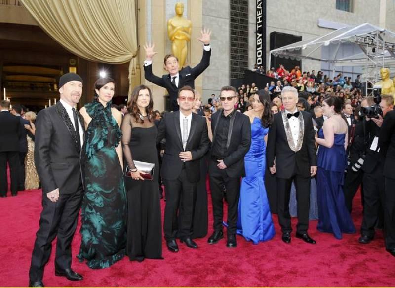 El actor Benedict Cumberbatch salta por detrás de U2 en la alfombra roja de la 86 edición de los Oscar.