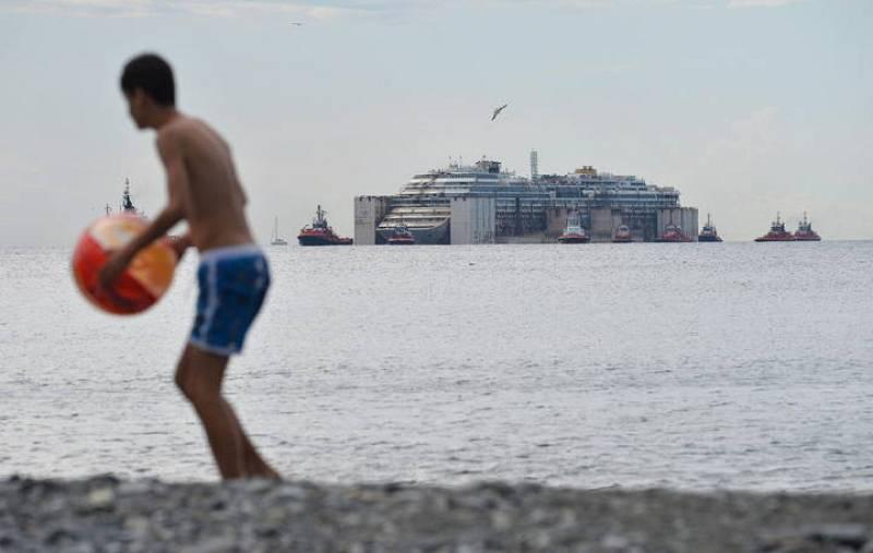 Un chico juega en la playa donde puede verse la llegada del Costa Concordia