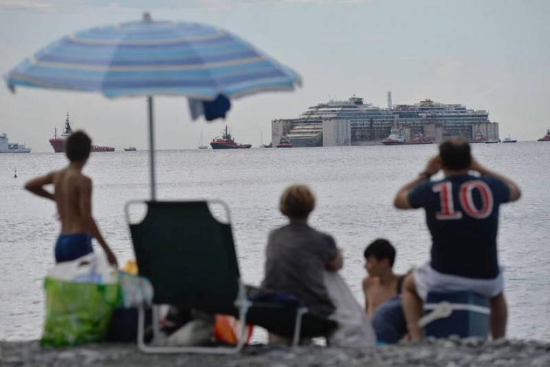 Varias personas miran desde la playa de Génova (Italia) la llegada del Costa Concordia.