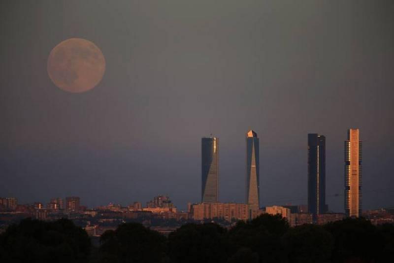 La superluna se levanta sobre las cuatro terres del Four Towers Business Area de Madrid.