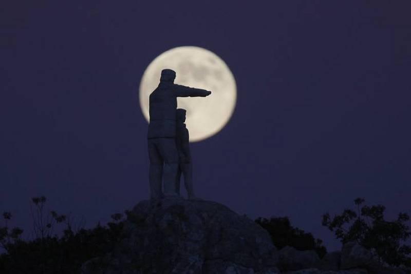 Estatua del monumento dedicado a los guardabosques recortada por la superluna en la Sierra de las Nieves (Málaga).