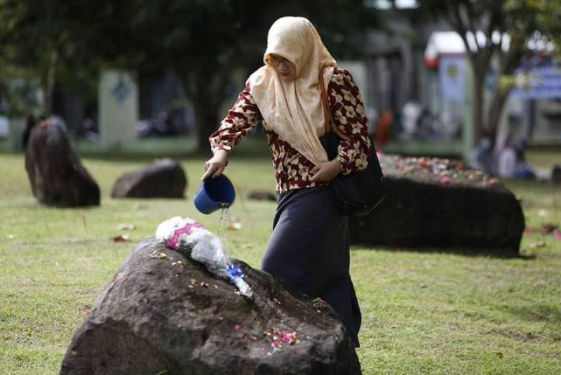 Una mujer vierte agua sobre una piedra que marca la fosa común de las víctimas del tsunami en Banda Aceh, la 'zona cero' del desastre