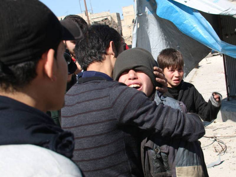 Varios niños se consuelan, asustados aún, tras el impacto de un barril bomba en un barrio de Alepo.