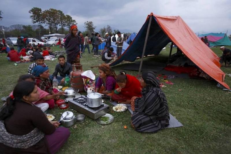 Miembros de una familia cenan frente a un refugio improvisado tras el terremoto en Katmandú, Nepal.