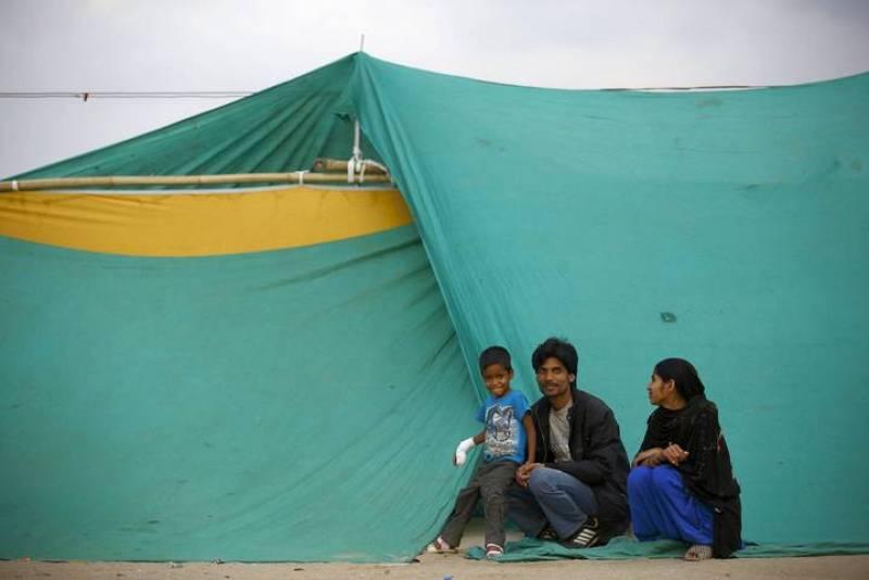 Un niño que resultó herido durante el terremoto de Nepal se sienta junto a su familia en un refugio improvisado en Katmandú.