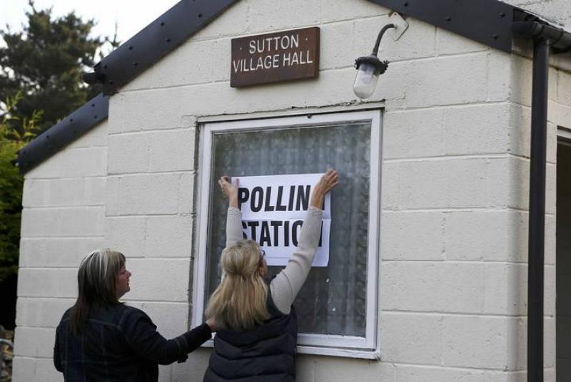 """Trabajadores electorales ponen el cartel de """"colegio electoral"""" en un edificio en Doncaster, norte de Inglaterra"""