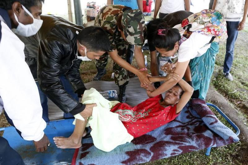 Soldados portan a un paciente de vuelta al hospital tras una evacuación durante el terremoto