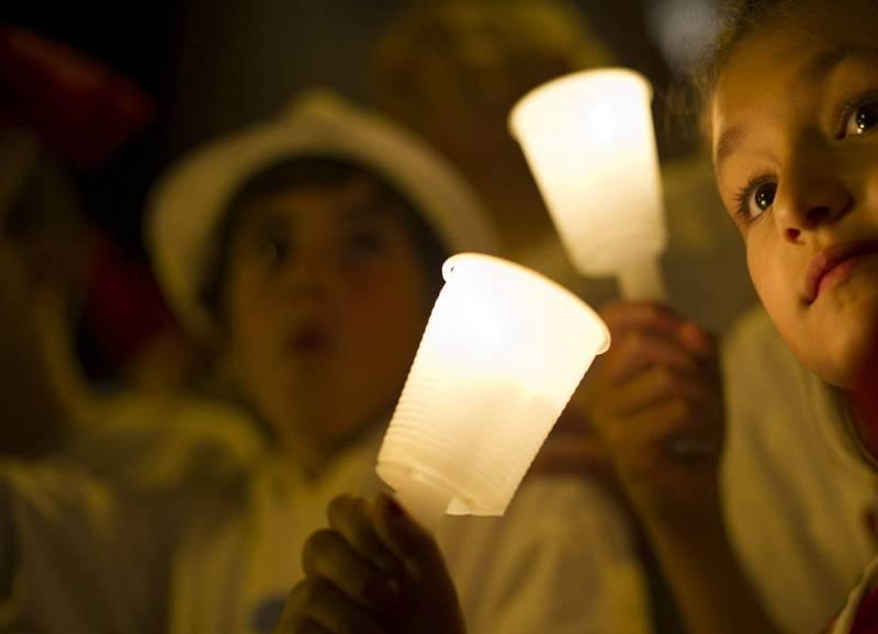 Un grupo de niños sujeta las tradicionales velas blancas para despedir la fiesta grande de Pamplona.
