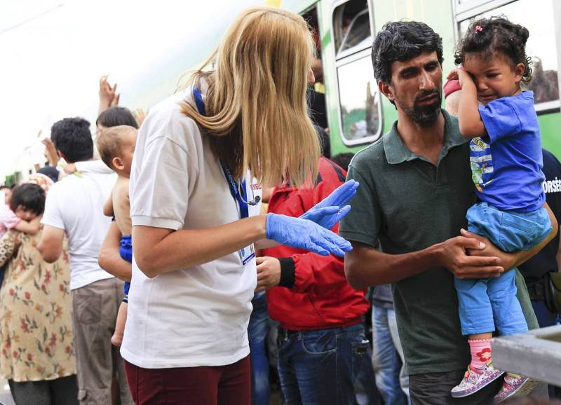 A medic speaks to a migrant holding his daughter at the railway station in the town of Bicske