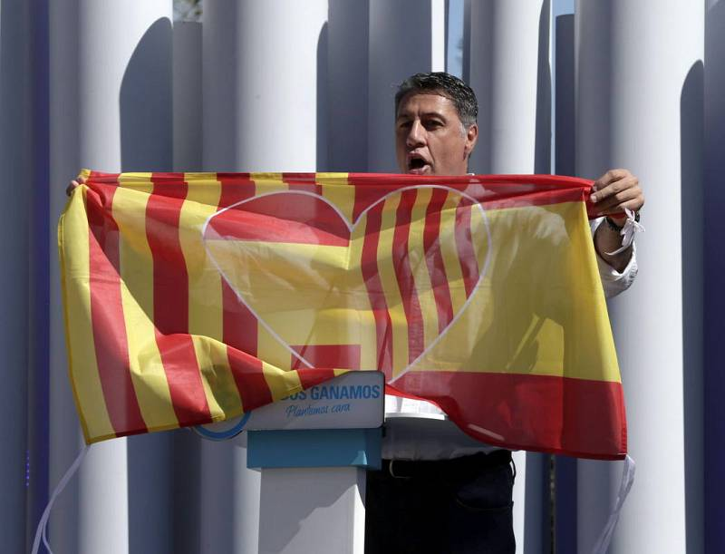 El candidato del PPC, Xavier García Albiol, muestra una bandera que une las de Cataluña y España, en un mitin en Badalona.
