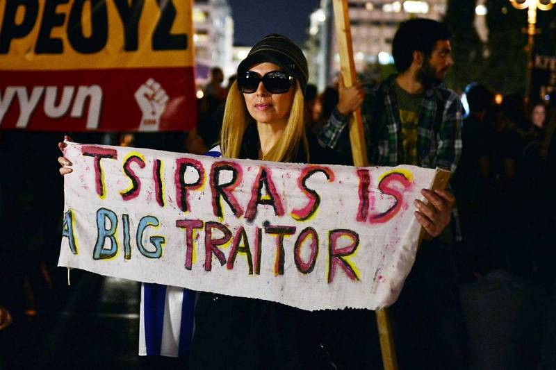 """Una mujer sostiene una pancarta en la que puede leerse """"Tsipras es un gran traidor"""" en una protesta ante el Parlamento contra el paquete de medidas aprobado."""
