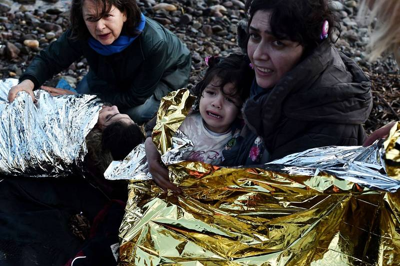 Una mujer con una niña en brazos llora al alcanzar la costa de la isla de Lesbos