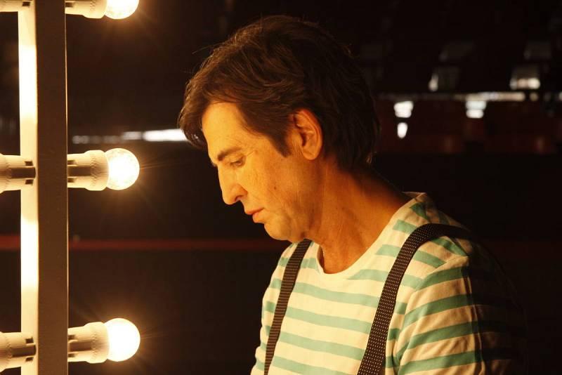 Frente al espejo de maquillaje, entre las bambalinas del escenario, Manolo Tena se prepara para el concierto