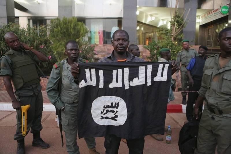 Oficiales de seguridad de Mali muestran una bandera portada por los terroristas