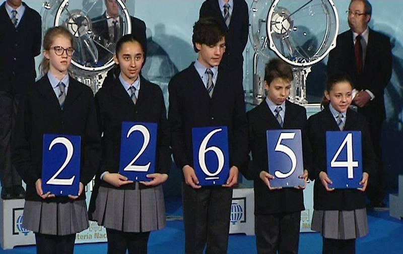 Los niños de San Ildefonso muestran el número 22.654, el primer premio del sorteo extraordinario de la lotería de El Niño, en el sorteo celebrado en el Círculo de Bellas Artes de Madrid.