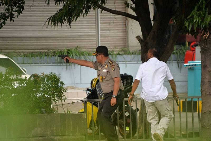 Un policía indonesio dispara durante el tiroteo que se ha desatado después de las explosiones