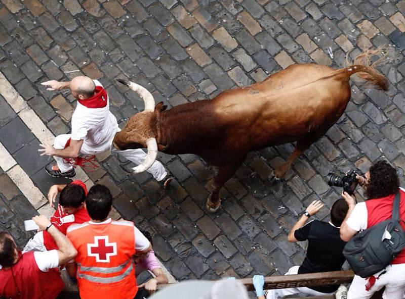 Un mozo intenta escapar del toro en el cuarto encierro