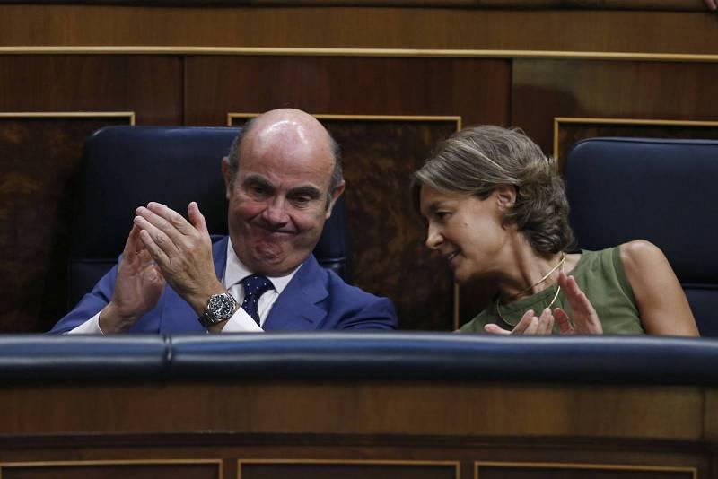 Los ministros en funciones de Economía, Luis de Guindos, y Agricultura y Pesca, Isabel García Tejerina, aplauden durante el discurso de investidura del presidente del Gobierno en funciones, Mariano Rajoy.