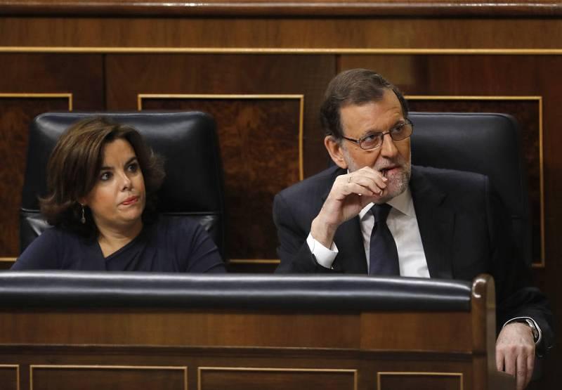 El presidente del Gobierno en funciones, Mariano Rajoy, acompañado por la vicepresidenta, Soraya Sáenz de Santamaría, escucha la intervención del portavoz del PSOE, Antonio Hernando.