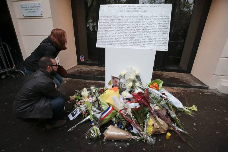 Dos personas depositan flores junto a la placa conmemorativa con los nombres de las víctimas en la sala Bataclan