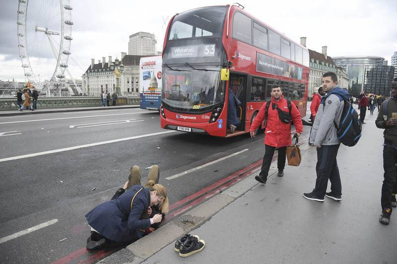 Una mujer asiste a una persona herida en el puente de Westminster