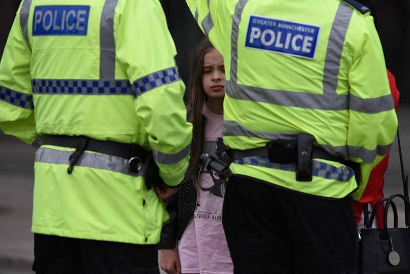 Una mujer y una niña ataviada con una camiseta de Ariana Grande hablan con dos agentes de policía en las inmediaciones del Manchester Arena
