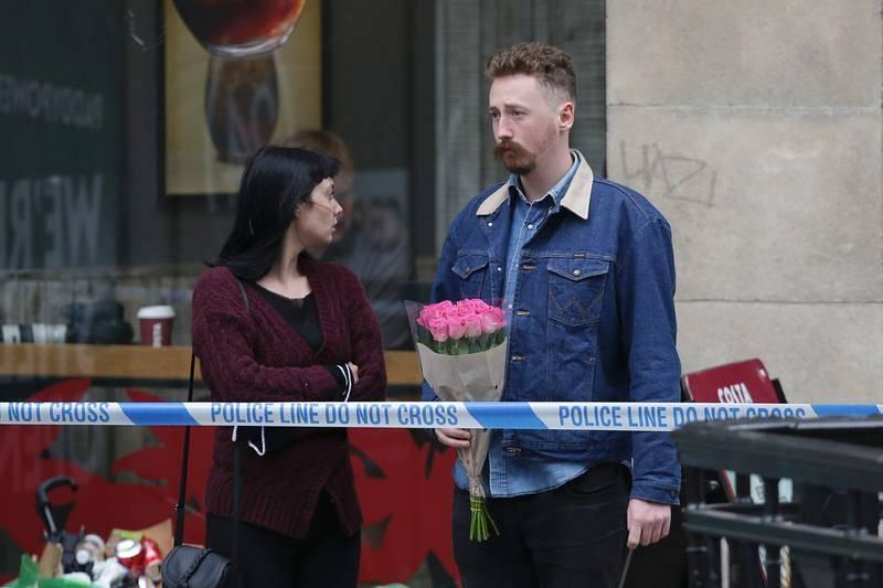 Una pareja con un ramo de flores tras el cordón policial situado en el extremo norte del Puente de Londres, en tributo de las víctimas del atentado