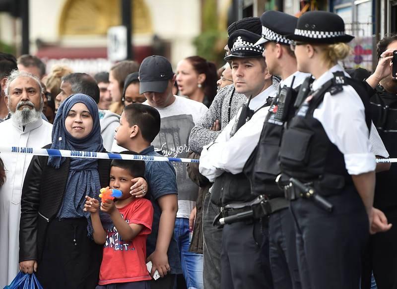 Un niño juega con una pistola de agua mientras la gente se arremolina tras el cordón policial en Barking Road, donde se ha producido una redada de la policía en el marco de la operación antiterrorista que se ha desarrollado en Londres tras los atenta