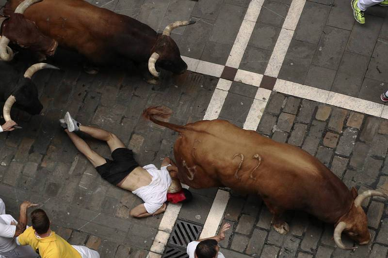 Los toros de la ganadería gaditada de Núñez del Cuvillo pasan por encima de un mozo en el tramo inicial de la calle Estafeta en el septimo encierro de los Sanfermines 2017