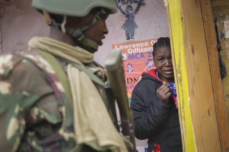 Una mujer aterrorizada se esconde de las revueltas entre partidarios de la oposición y la Policía