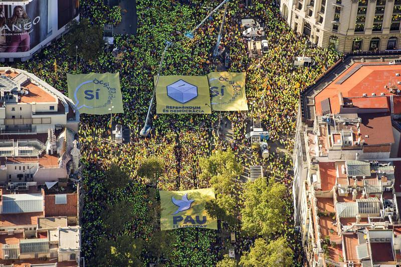 """Cuatro pancartas gigantes se han desplegado en la manifestación de la Diada, con los lemas """"Paz y libertad"""", """"Referéndum es democracia"""" y """"Sí"""". Se han encontrado en el centro de la cruz que han hecho los manifestantes"""