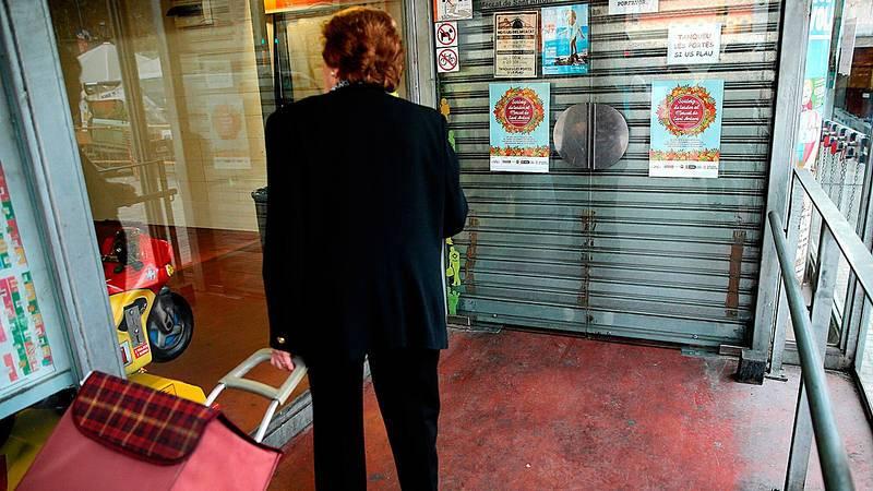 Una mujer ante las puertas del Mercado de Sant Antoni