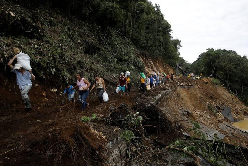 Gente transitando por una carretera dañada por las lluvias