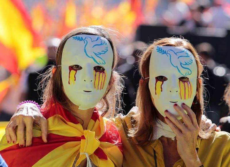 Dos mujeres con máscaras durante la marcha en defensa de la unidad de España